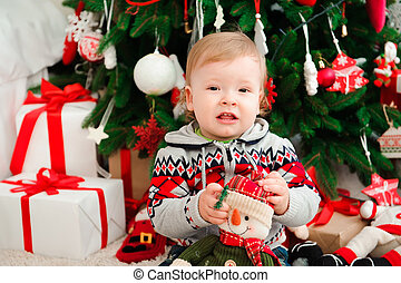 Family New year celebration. The little boyl at the Christmas tree.