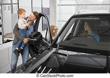 Family observing new automobile in car dealership.