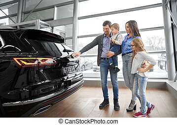 Family observing new black car in showroom.