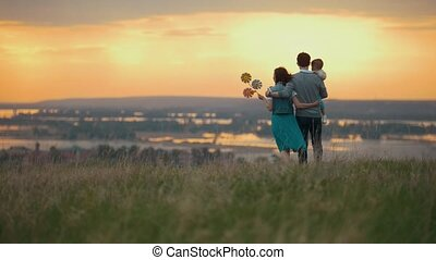Family of 3 people resting in nature, mom dad and son go and cuddle, orange sunset, telephoto shot