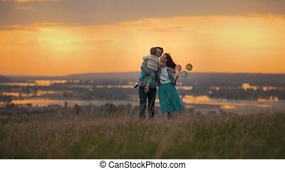 Family of 3 people walking on the field on a summer evening, mom kissing her son, orange sunset, telephoto shot