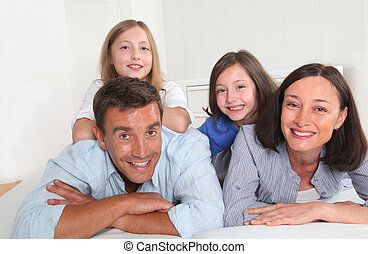 Family of 4 people laying down couch