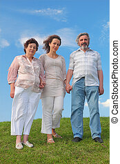 family of adult woman and her parents standing on lawn and holding for hands, blue sky