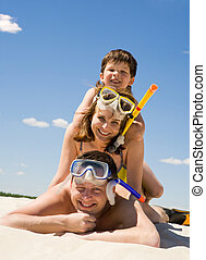 Portrait of happy family in goggles and flippers lying on sandy beach against blue sky