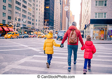Family of father and little kids on Times Square during their vacation in New York City