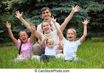 family of five rejoice outdoor in summer sit on grass, hands...