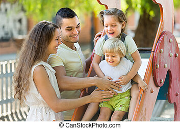 Family of four at playground - Happy cheerful family of four...