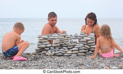 family of four building wall of stones on beach, sea surf in background