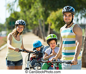 Family of four cycling on street