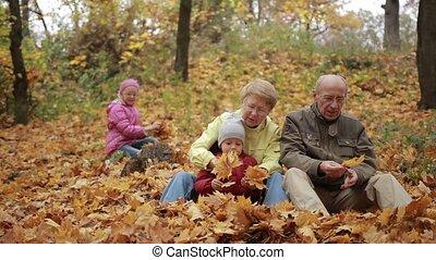 Family of four enjoying golden leaves in autumn
