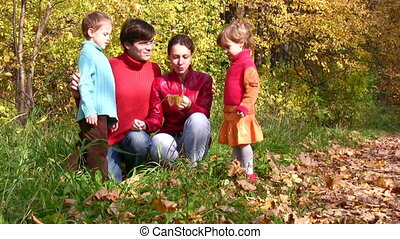 family of four exploring something in autumn park