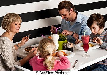 Family of four having meal in restaurant