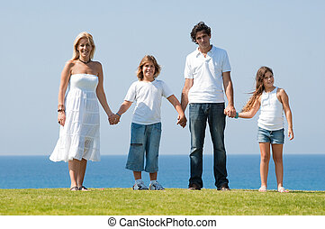 Family of four holding hands