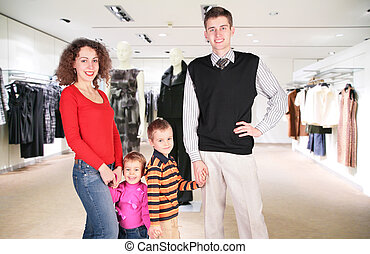 family of four in woman clothes in shop