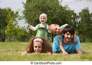 family of four lies on grass 2
