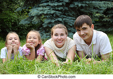 family of four lying on grass and looks