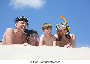 family of four lying on sand with snorkeling masks