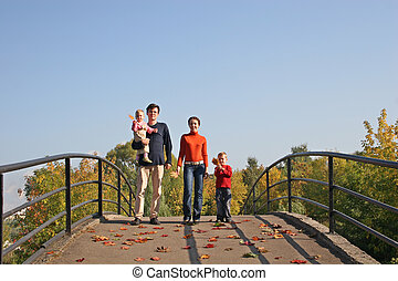 family of four on autumn bridge