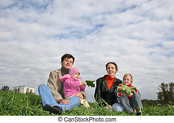 family of four on autumn grass