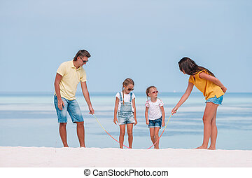 Family of four on beach vacation have fun