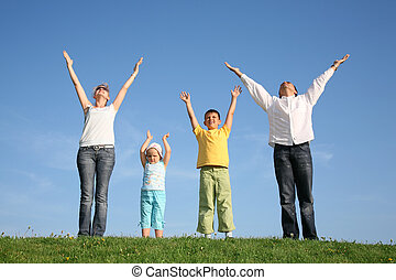 family of four on grass with hands up