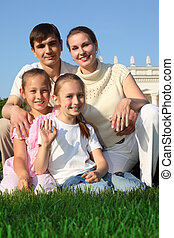 family of four outdoor in summer sits on grass