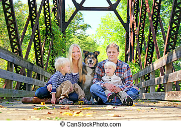 Family of Four People and Dog Sitting On Bridge in Autumn -...