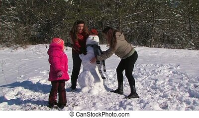 Family of four run around upside down snowman at winter day
