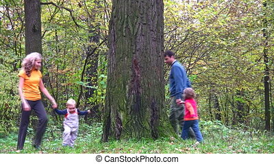 family of four running around big tree. Autumn.
