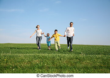 family of four running grass sky