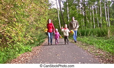 family of four running in autumn park