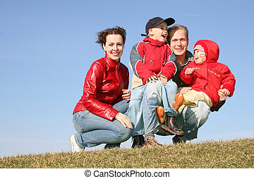 family of four sit on spring meadow
