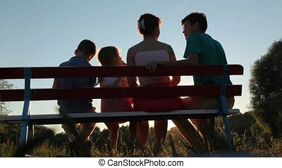 family of four sits on bench in park