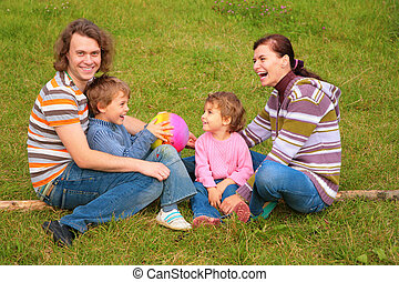 Family of four sits on grass