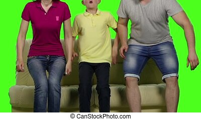 Family of four sitting on the couch with a smile. Green screen. Slow motion