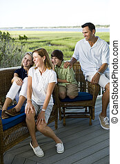Family of four sitting together outdoors on terrace