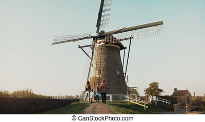 Family of four stand by huge old Dutch wind mill. Amazing...