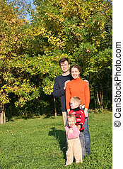 family of four stand in autumn park