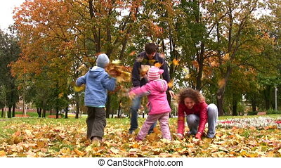 family of four throw autumn leaves