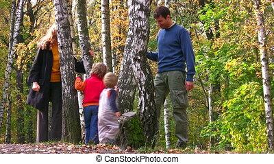 family of four walking around birch