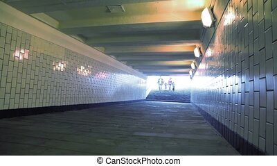 family of four walking in underground passage to camera, joined hands
