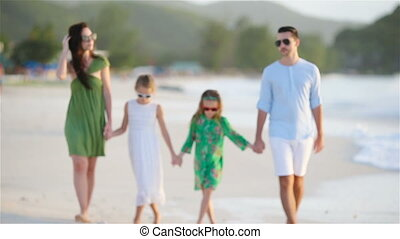 Family of four walking on white beach