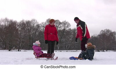 family of four with sleds