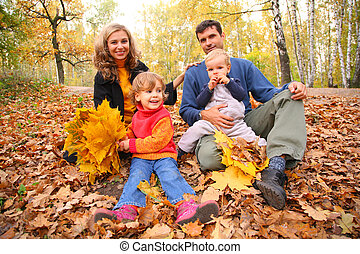 Family of four with yellow maple leaves sits in wood in autumn