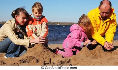 family of mon, dad, son and daughter build hills of sand together on river beach