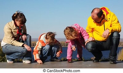 family of mother, father, daughter and son sits and draws on asphalt chalk against kind of river and sky