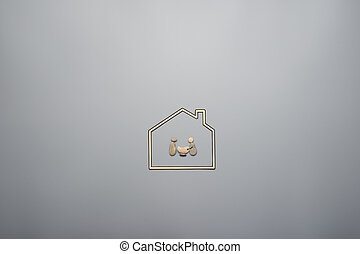 Family of mum, dad and baby in a stroller made of pebbles in a paper cut house