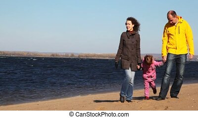 family of mum, daddies and daughter stands on sandy to river...