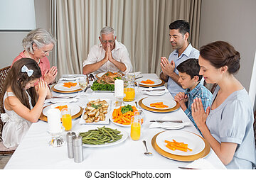 Family of six saying grace before meal at dining table in...