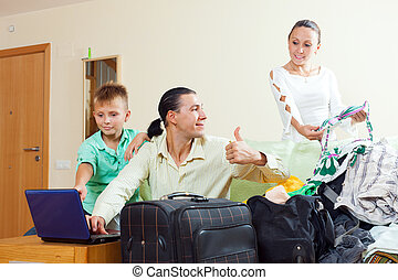 family of three choosing resort and packing suitcases